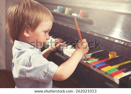 Young boy painting piano keys with brush.