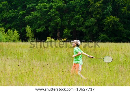 Young boy playing badminton in a meadow with a forest in background