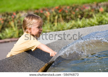 young boy playing in a public fountain