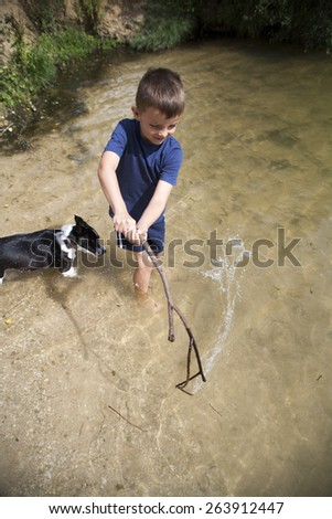 Young boy playing in the water with his dog using a big stick