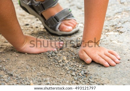 Young boy playing with pebbles on the floor