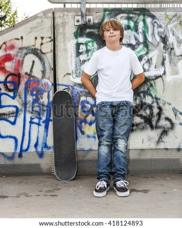 young boy relaxes with his skate board at the skate park