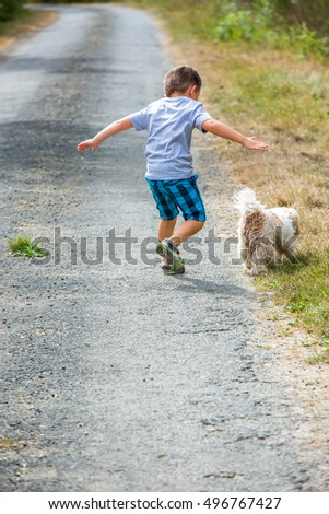 Young boy running down the road accompanied by a small white dog