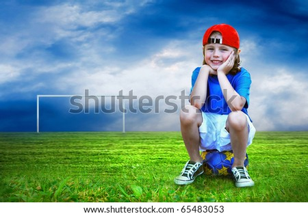 Young boy seating on the ball in green field