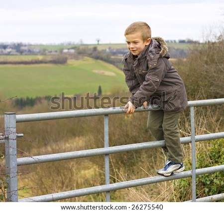Young boy sitting on gate looking at countryside