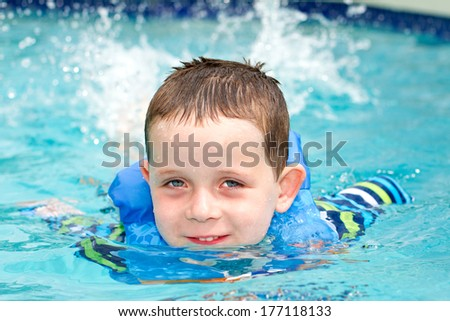 young boy smiling whilst swimming in the pool