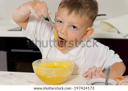 Young boy taking a taste of the cake mix as he stands in the kitchen learning how to make his favorite cake