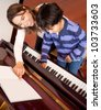 Young boy taking piano lessons at home - stock photo
