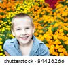 young boy with blue eyes on background variety of flowers in the park - stock photo