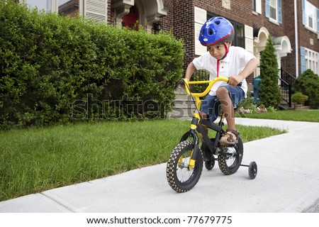 Young boy with helmet riding his first bicycle with training wheels