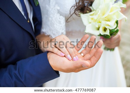 Young bride and groom holding hands on wedding day. Close up of male and female hands with golden rings and bouquet of fresh white flowers. Horizontal colour image of new family after wedding ceremony