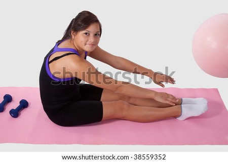 Young brunette aboriginal teen girl wearing workout attire sitting on pink mat reaching for toes