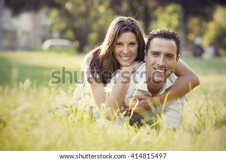 young brunette couple having fun together at the park