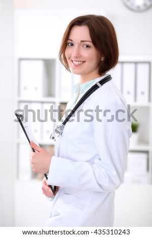 Young brunette female doctor standing with clipboard and smiling at hospital office. Health care, insurance and help concept. Physician ready to examine patient