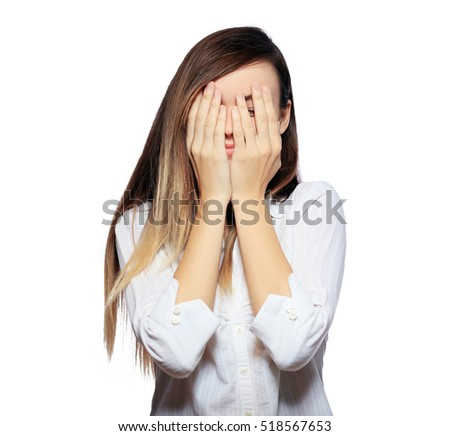 stock photo scared hiding behind hands from something unseen