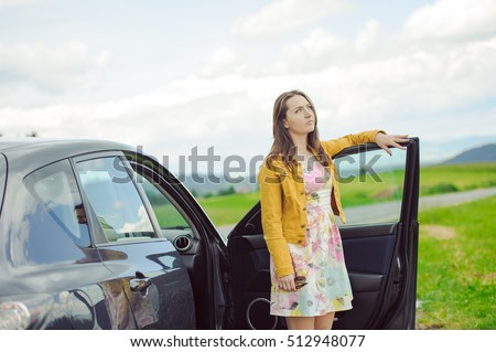Young brunette girl standing next to the car with open door