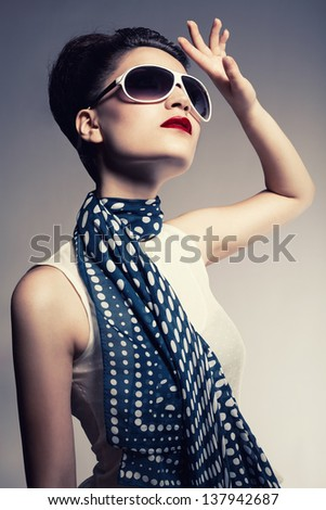 young brunette model wearing a sunglasses and a scarf posing on gray background