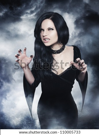 Young brunette woman as sexy vampire on  night background