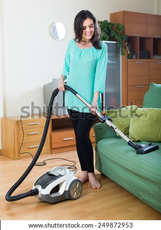 Young brunette woman cleaning with vacuum cleaner at home