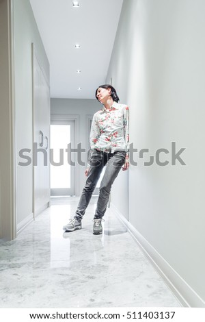 Young Brunette Woman  Leaning on the Wall