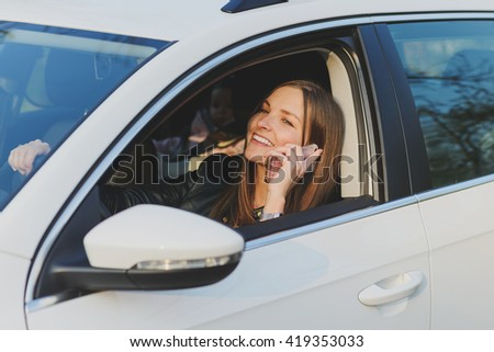 young brunette woman using mobile phone while driving a car
