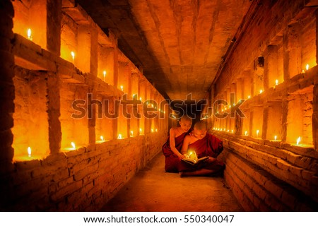 Young Buddhist Monk are reading a book with light from candle and sun light from outside to inside pagoda of old bagan with statue in mandalay historical park, mandalay, myanmar