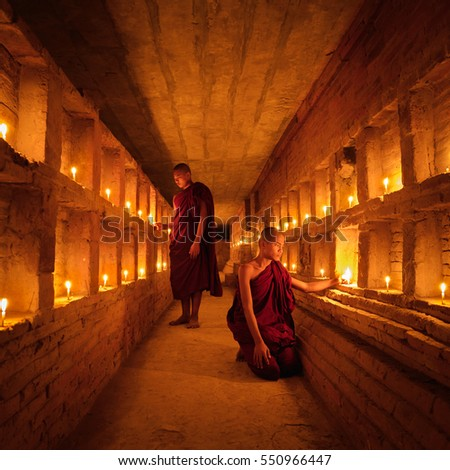 Young Buddhist Monk with light from candle inside pagoda of old bagan with statue in mandalay historical park, Bagan Mandalay, Myanmar