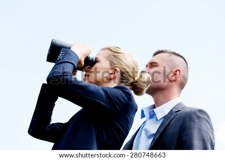 Young business couple looking at the sky