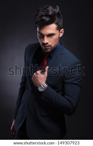 young business man holding a hand on the lapel of his jacket and looking at the camera. on a black background