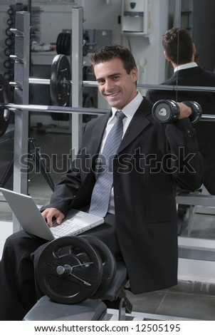Young business man keeping himself fit while working - doing a shoulder press and smiling at the camera