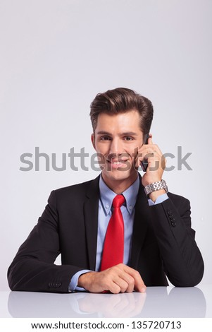 young business man sitting at the desk and speaking on the phone with a smile on his face