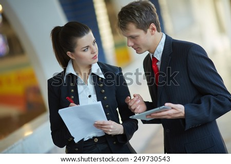 Young business woman and businessman studying documents in the hallway