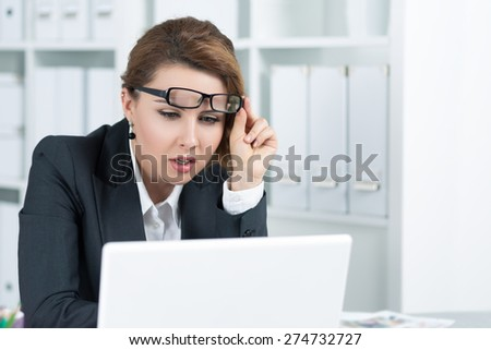 Young business woman looking intently at laptop monitor seeing something unusual