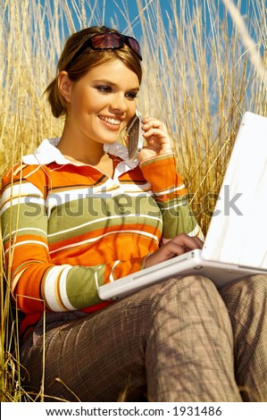 Young business woman relaxing, working on laptop computer and talking cell phone on meadow