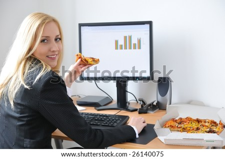 Young business woman siting at work table and eating pizza