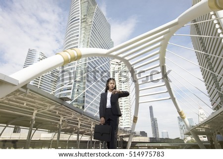 Young business woman stand awaiting meeting at skyline bridge in business town , looking wristwatch to check meeting time