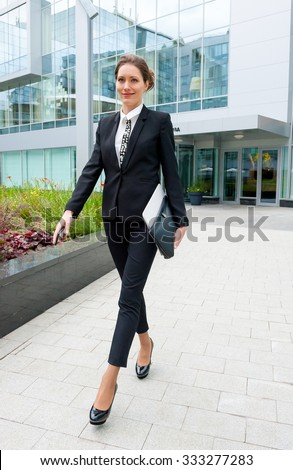Young business woman walking near office building
