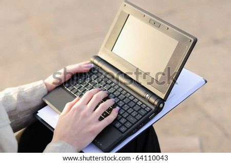Young business woman working on a laptop sitting on the street
