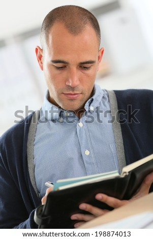 Young businessman at work checking on agenda