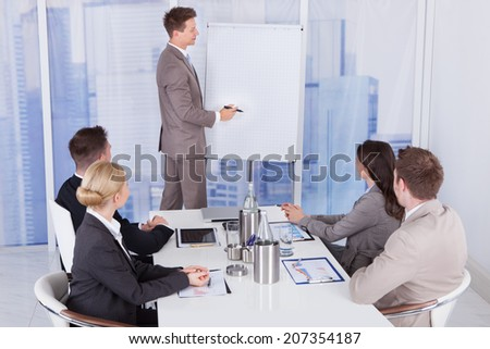 Young businessman giving presentation to colleagues at office