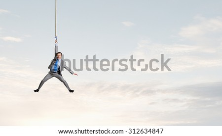 Young businessman hanging on rope high in sky