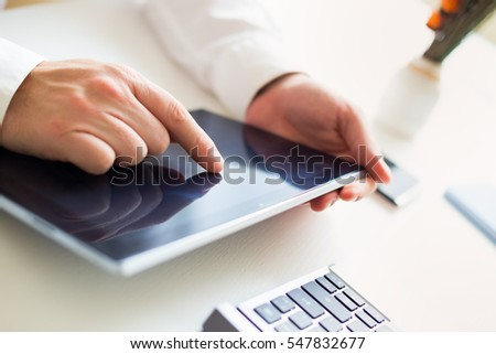 Young businessman holding a computer tablet and touching a screen