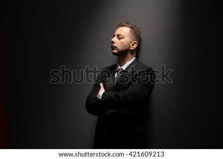 Young businessman in black suit posing with crossed or folded arms and looking away over grey background in studio.
