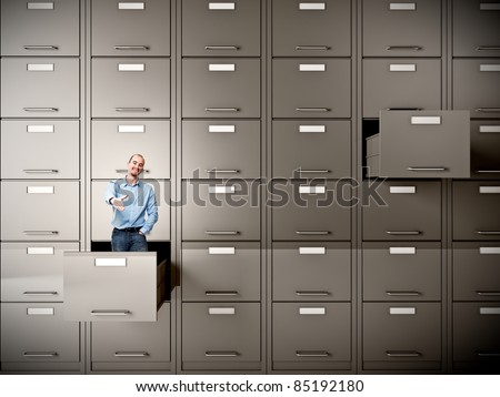 young businessman in file cabinet drawer