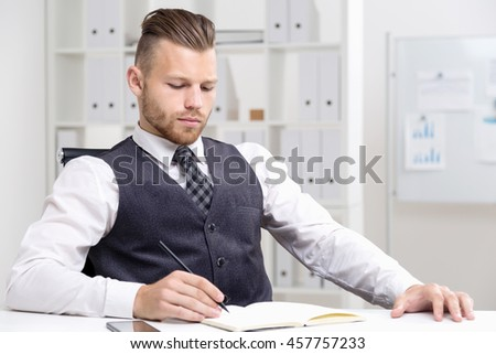 Young businessman in formal clothes sitting in armchair and writing in notebook with pen. His smartphone on table. Concept  of business process