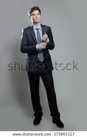 Young businessman in gray suit thinking or dreaming, on gray background