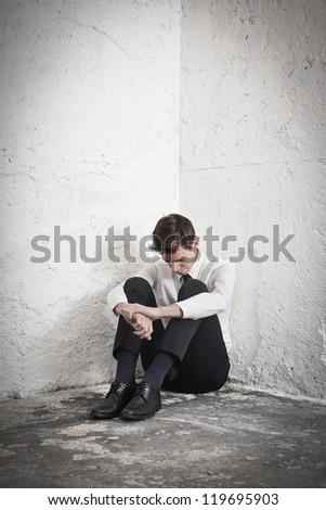 Young businessman in the corner of a basement