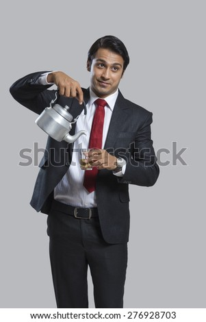 Young businessman pouring tea in glass over gray background