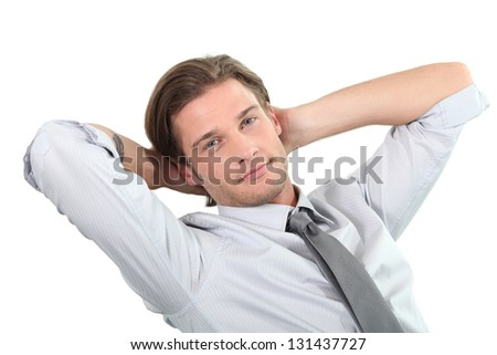 Young businessman sitting with arms behind head.