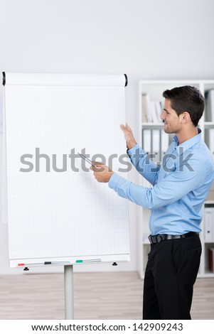 Young businessman standing near a flipchart and explaining the numbers.